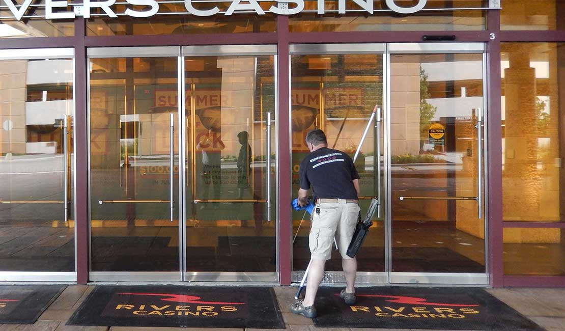 man cleaning door at casino